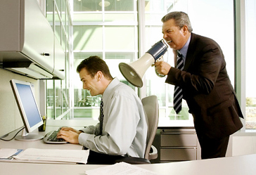 A man shouts into a megaphone just behind a long-suffering developer working at a computer
